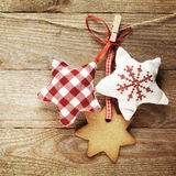 Gingerbread cookies and christmas decorations hanging over wooden background Stock Image