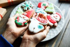 Gingerbread cookies for christmas, new year in kids hands on the wooden table. Festive, sweet pastry, delicious biscuits. royalty free stock images