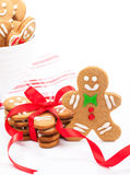 Gingerbread Cookies. Cute Christmas gingerbread cookies on white with napkin and bowl. Some cookies tied with red ribbon to make a delicious gift stock photos