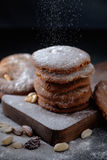 Gingerbread cookies dusted with icing sugar on a wooden table.  Stock Image