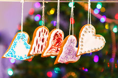 Gingerbread cookies hanging with Christmas tree on background. Stock Photo