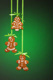 Gingerbread Cookies. Hanging by green ribbon over a green background royalty free stock images