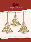 Gingerbread cookies hanging over Christmas card Royalty Free Stock Photography