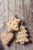 Gingerbread cookies hanging over wooden background. Christmas decoration Stock Images