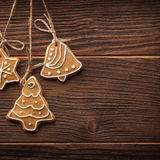 Gingerbread cookies hanging over wooden background Stock Photo
