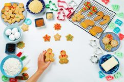 Gingerbread cookies with ingredients for baking and woman`s hand Royalty Free Stock Photography