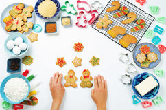 Gingerbread cookies with ingredients for baking and woman`s hand Stock Photos