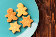 Gingerbread cookies man and star shape in turquoise plate on woo. Den table with copyspace Royalty Free Stock Image