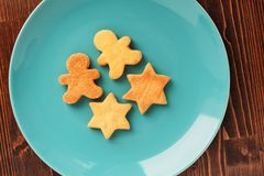 Gingerbread cookies man and star shape in turquoise plate on woo. Den table overhead view Stock Image