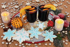 Gingerbread Cookies and Mulled Wine. Christmas snowflake gingerbread cookies, mulled wine, orange pomanders and frosted apple decorations, with candles, holly Royalty Free Stock Images