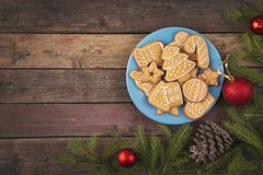Gingerbread cookies on a plate. Table top shot of nicely decorated Christmas cookies on a plate with some fir branches, pine cones and Christmas decoration stock photography
