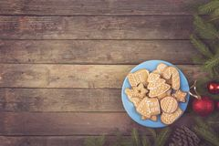 Gingerbread cookies on a plate. Table top shot of nicely decorated Christmas cookies on a plate with some fir branches, pine cones and Christmas decoration stock image
