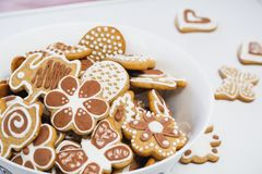 Gingerbread cookies in the shape of an Easter bunny, butterflies and flowers, covered with white and chocolate icing-sugar royalty free stock images