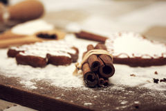 Gingerbread cookies, spices and flour over wooden background. Vintage Christmas background with gingerbread cookies, spices and flour over wooden background royalty free stock images