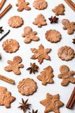 Christmas composition - gingerbread cookie, anise and cinnamon on wooden table. Gingerbread cookies and spices over white background close up stock image
