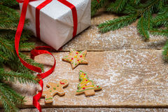Gingerbread cookies surrounded by spruce and a gift for Christma. S on old wooden table Royalty Free Stock Images