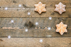 Gingerbread cookies on wooden background with snowflakes with space for your text Royalty Free Stock Photo
