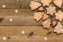 Gingerbread cookies on wooden background with snowflakes with space for your text Royalty Free Stock Photos