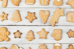 Gingerbread cookies world. Top view of different shapes of nicely decorated Christmas cookies on wooden background stock photo