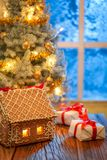 Gingerbread cottage, Christmas tree and presents with blue frozen window. On wooden table stock photo