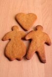 Gingerbread couple. Gingerbread man and woman with  gingerbread heart on wooden surface Royalty Free Stock Photos