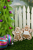 Gingerbread couple at fence and tree Royalty Free Stock Photography