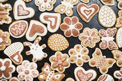 Gingerbread, covered with white and chocolate icing-sugar on a black surface royalty free stock image