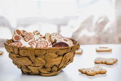 Gingerbread, covered with white and chocolate icing-sugar, and easter chicken eggs in a brown wicker basket royalty free stock photography