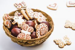 Gingerbread, covered with white and chocolate icing-sugar, and easter chicken eggs in a brown wicker basket royalty free stock images