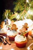 Gingerbread cupcakes, gingerbread cookies and Christmas lights. Closeup view, selective focus stock image