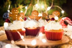 Gingerbread cupcakes, gingerbread cookies and Christmas lights. Closeup view, horizontal composition, selective focus royalty free stock photos