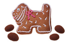 Gingerbread doggie. The image of a gingerbread doggie with a red and white pattern and four chocolates on a white background Royalty Free Stock Image