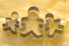 Gingerbread family/children cutters on orange background Royalty Free Stock Photos
