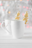Gingerbread fir-tree put on a white cup with hot chocolate on the background of bokeh and snow Stock Images