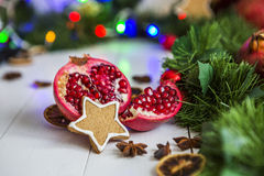 Gingerbread in the form of stars, cut red pomegranate, cinnamon, dried lemons on white table on a background of garland and light Stock Image