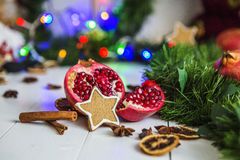 Gingerbread in the form of stars, cut red pomegranate, cinnamon, dried lemons on white table on a background of garland and light Royalty Free Stock Photography