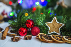 Gingerbread in the form of stars, red Christmas balls, dried lemons, cinnamon and green garland and lights Stock Photo