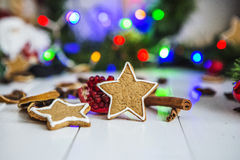 Gingerbread in the form of stars, red Christmas balls, dried lemons, cinnamon and green garland and lights Stock Images