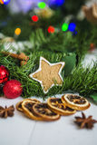 Gingerbread in the form of stars, red Christmas balls, dried lemons, cinnamon and green garland and lights Royalty Free Stock Images
