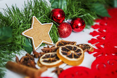 Gingerbread in the form of stars, red Christmas balls, dried lemons, cinnamon and green garland and lights Royalty Free Stock Image
