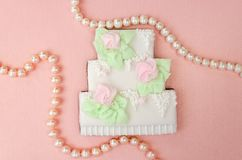 Gingerbread in the form of a three-tiered wedding cake with pearl beads. On a pearly pink background stock photography