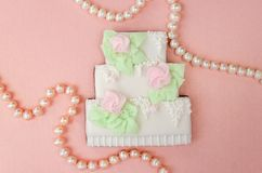 Gingerbread in the form of a three-tiered wedding cake with pearl beads. On a pearly pink background stock images