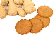 Gingerbread and ginger. Gingerbread cookies and whole ginger rhizome over white Stock Photos