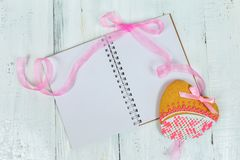 Gingerbread heart and a book with blank pages. wooden background. Holiday Cookies. Royalty Free Stock Photography