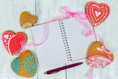 Gingerbread heart and a book with blank pages. wooden background. Holiday Cookies. Royalty Free Stock Images