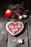 Gingerbread heart with candle cinnamon stars pine twig christmas bulb on wooden floor Royalty Free Stock Photo