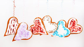 Gingerbread heart cookies hanging on white background. Royalty Free Stock Image