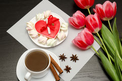 Gingerbread heart shaped pink tulips and a mug of coffee. Black table. top view Stock Image