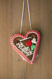 Gingerbread heart with wooden background. I love you written on a gingerbread heart hanging on wooden wall Royalty Free Stock Images
