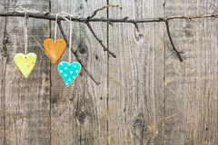 Gingerbread hearts hanging off a bare branch. Gingerbread hearts tied with bakers twine hanging off a bare branch on rustic wooden background Royalty Free Stock Photography